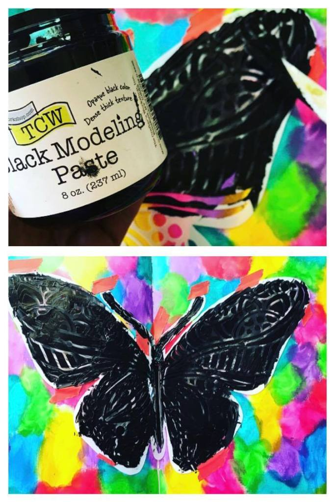 adding black modeling paste through the butterfly stencil using a spatula