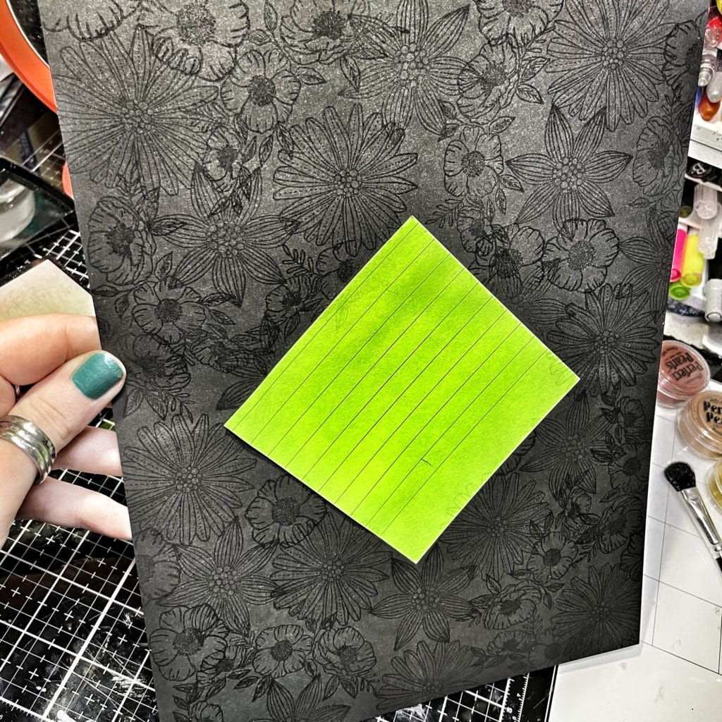 completed stamped background with VersaMark ink on black card stock