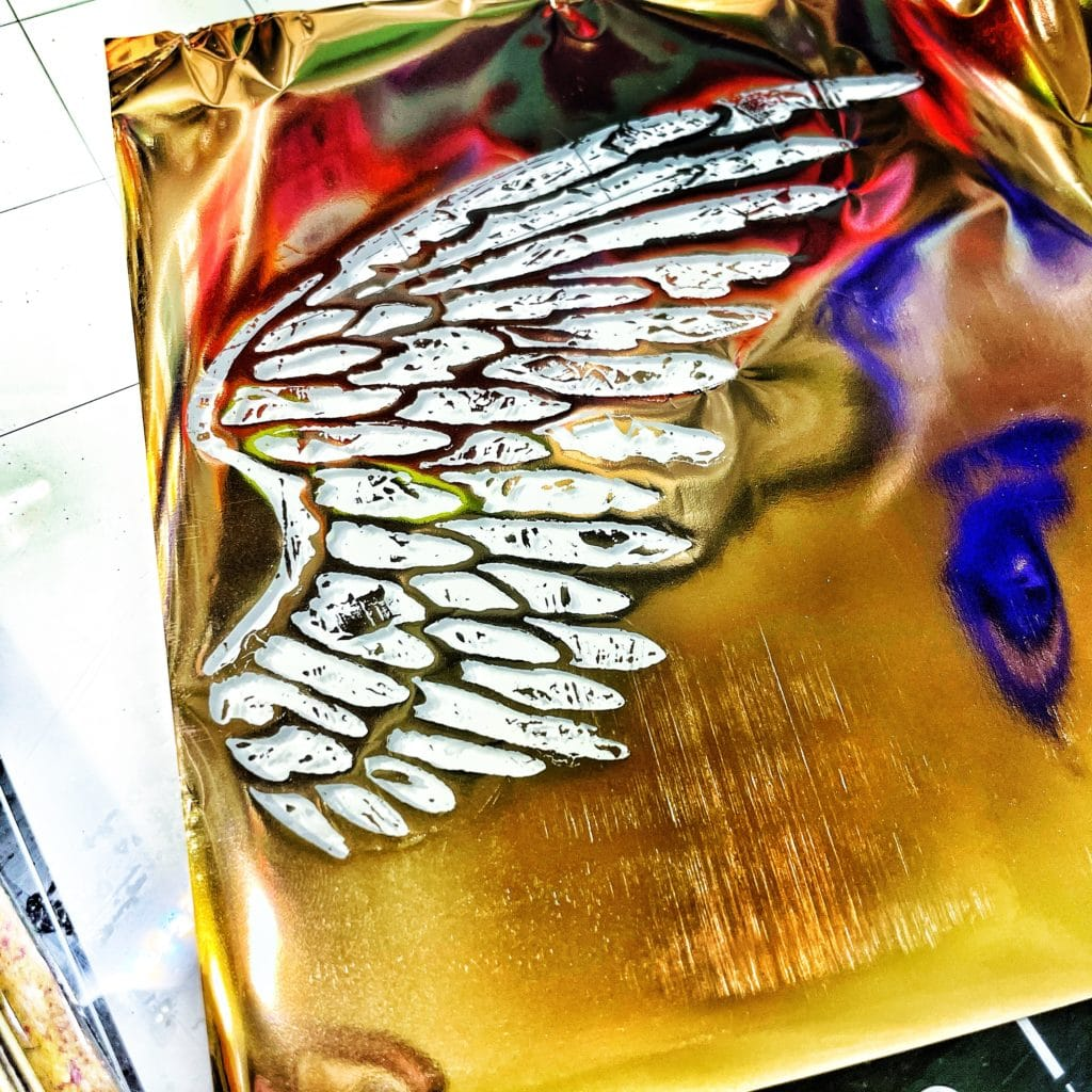 gold wing revealed from foil burnishing over 12x12 TCW616 Angel Wings Stencil