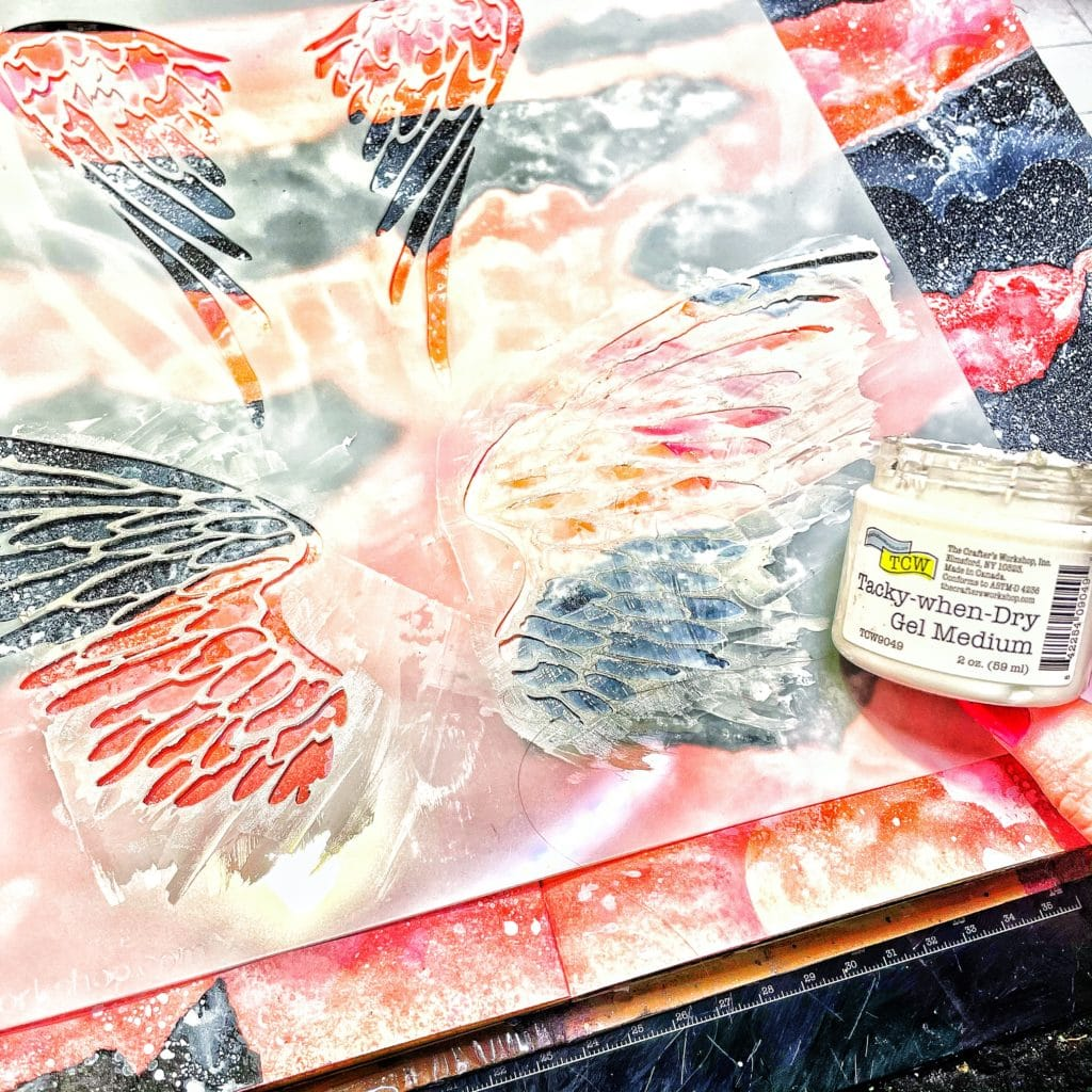 even layer of TCW 9049 Tacky When Dry Dry Gel Medium through 12x12 TCW616 Angel Wings Stencil with a palette knife