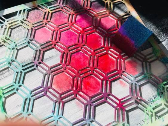adding pink paint through a honeycomb stencil