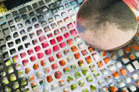 adding white painted squares through a stencil using a makeup sponge
