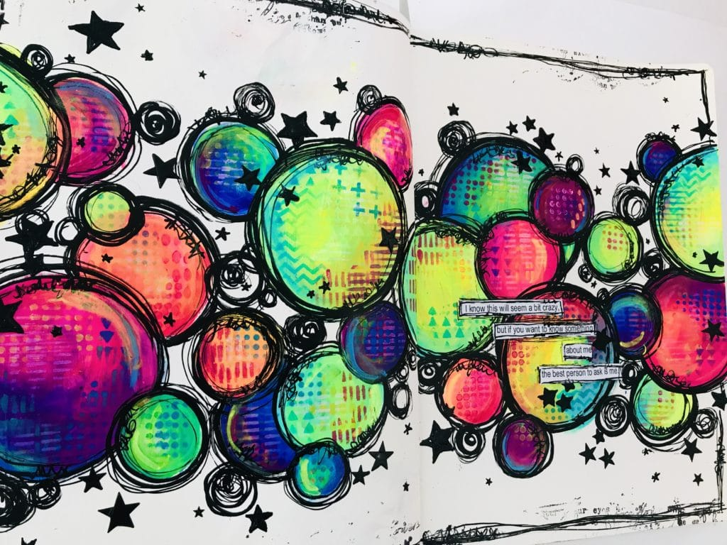 Art journal page with overlapping circles in all colors with textures created by using stencils