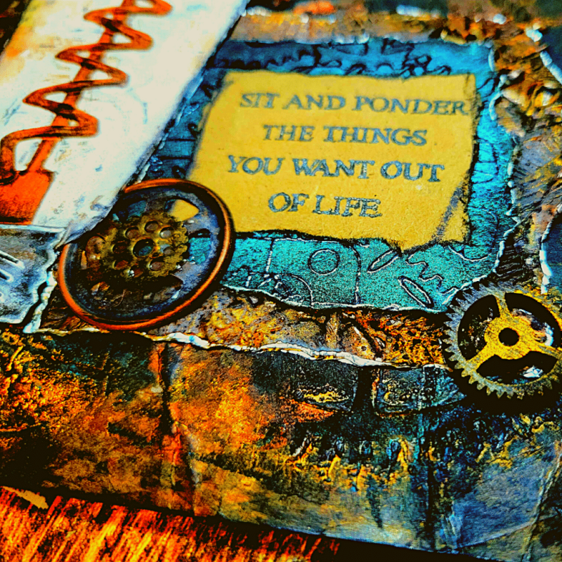 Close up image of the bottom right corner of the completed artwork, showing the sentiment, layers of background, wooden and metal gear embellishments and all of the details in their grungy gloriousness.