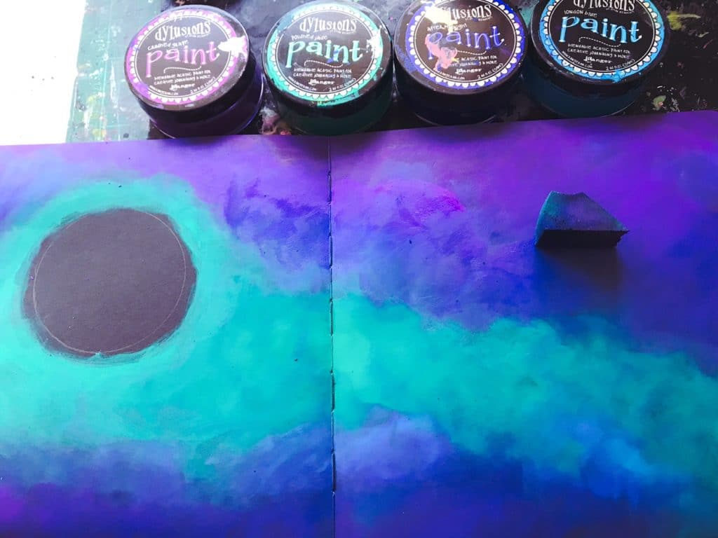 adding deep purple, blue and aqua paint to the background using a sponge