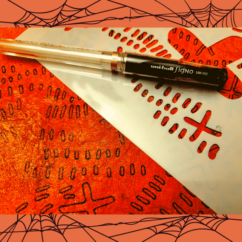A black uni-ball Signo UM-153 pen lays upon Stencil TCW940 Xtrail. The stencil lays upon the hand-made, orange-sprayed paper with black stenciling over the page (using the Xtrail stencil).