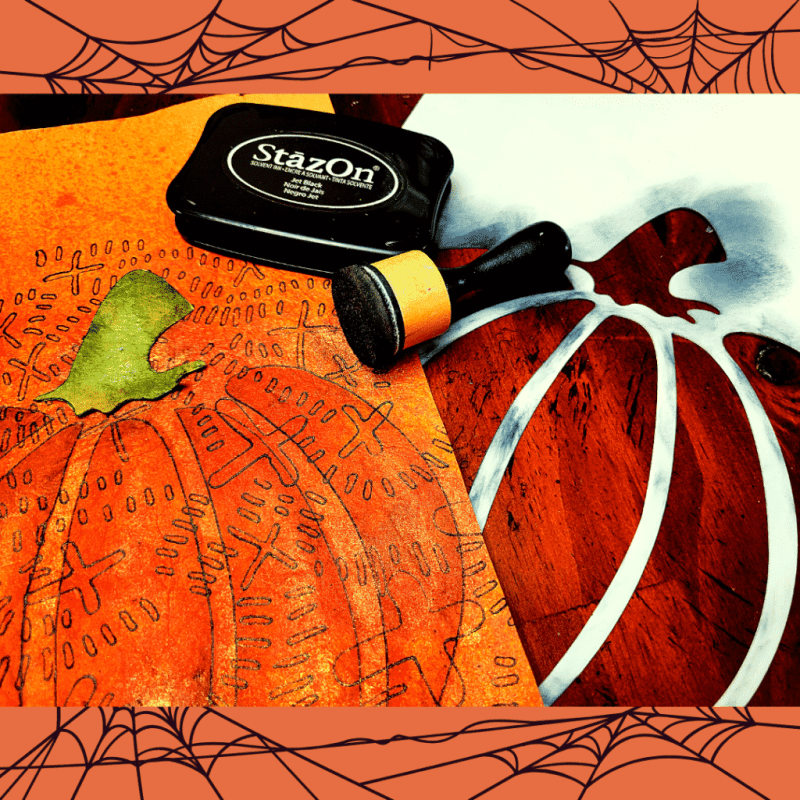 A black Stayz-On ink pad and distress ink applicator lay on top of the Xtrail stenciled paper and the TCW878 Jack-o-Lantern stencil. The green stem has been outlined and cut out of the same green paper that was used to create the grass.