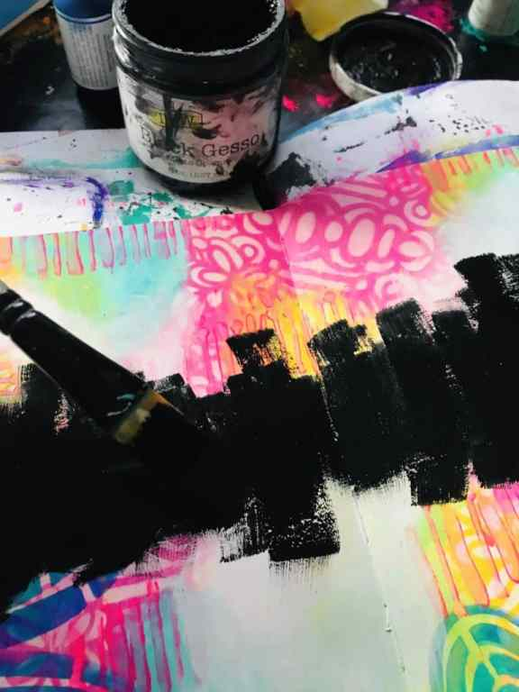 adding black gesso with a brush through the center of the page from left to right