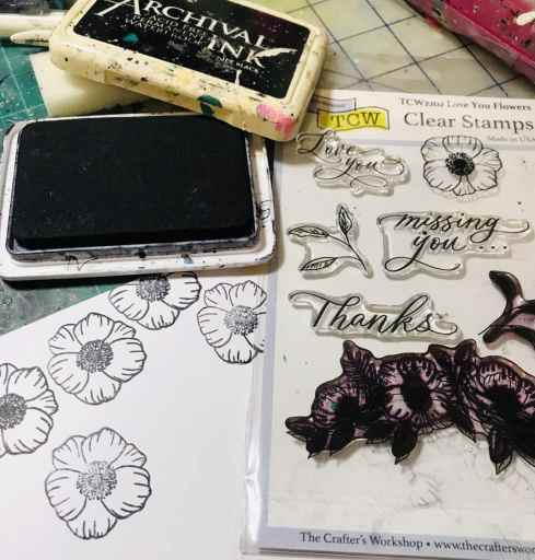 stamping flowers onto white cardstock using archival ink and then cutting them out
