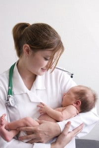 Smiling young doctor holding a beautiful newborn baby.