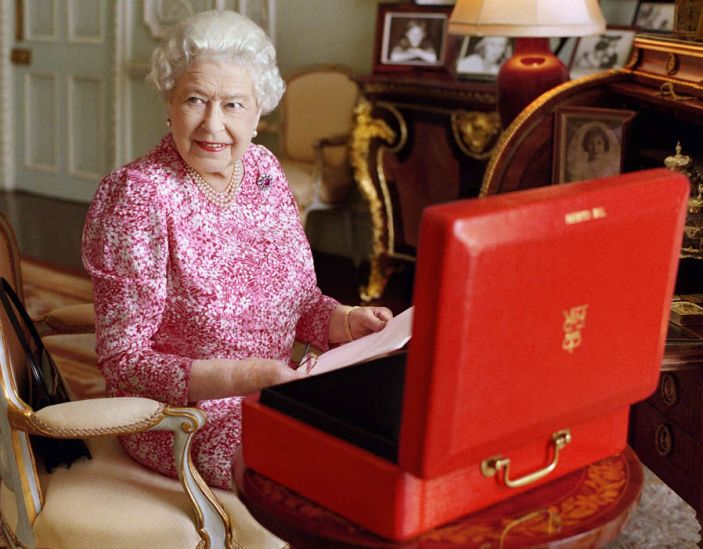 The Queen sits at her desk with her red box of official government papers. Mary McCartney