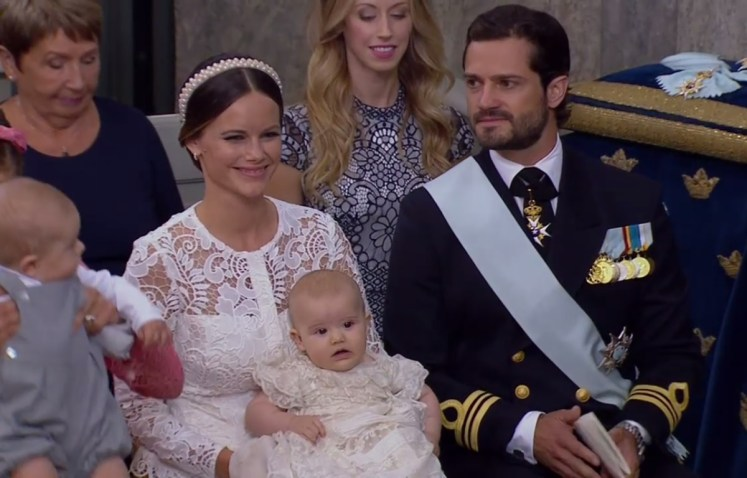 Proud Princess Sofia holds Prince Alexander at his christening today, sitting by her husband, Price Carl Philip (SVT/Kungahuset)