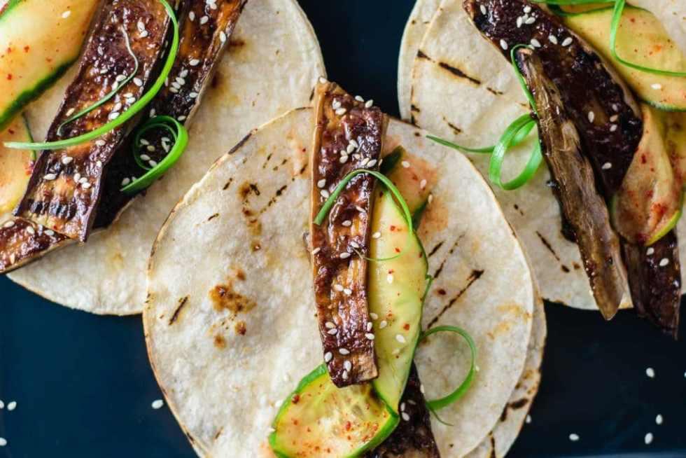 prepared miso-glazed eggplant tacos (nasu dengaku tacos) with marinated cucumbers and scallions, close up