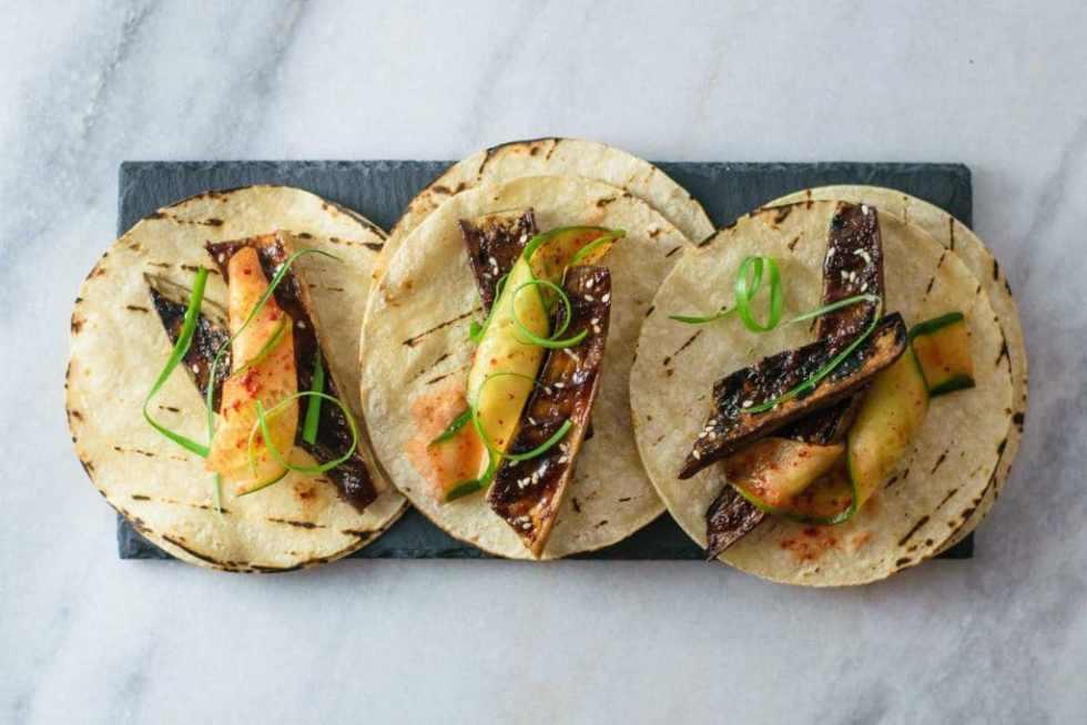 miso glazed eggplant tacos with chili marinated cucumber and scallions on slate