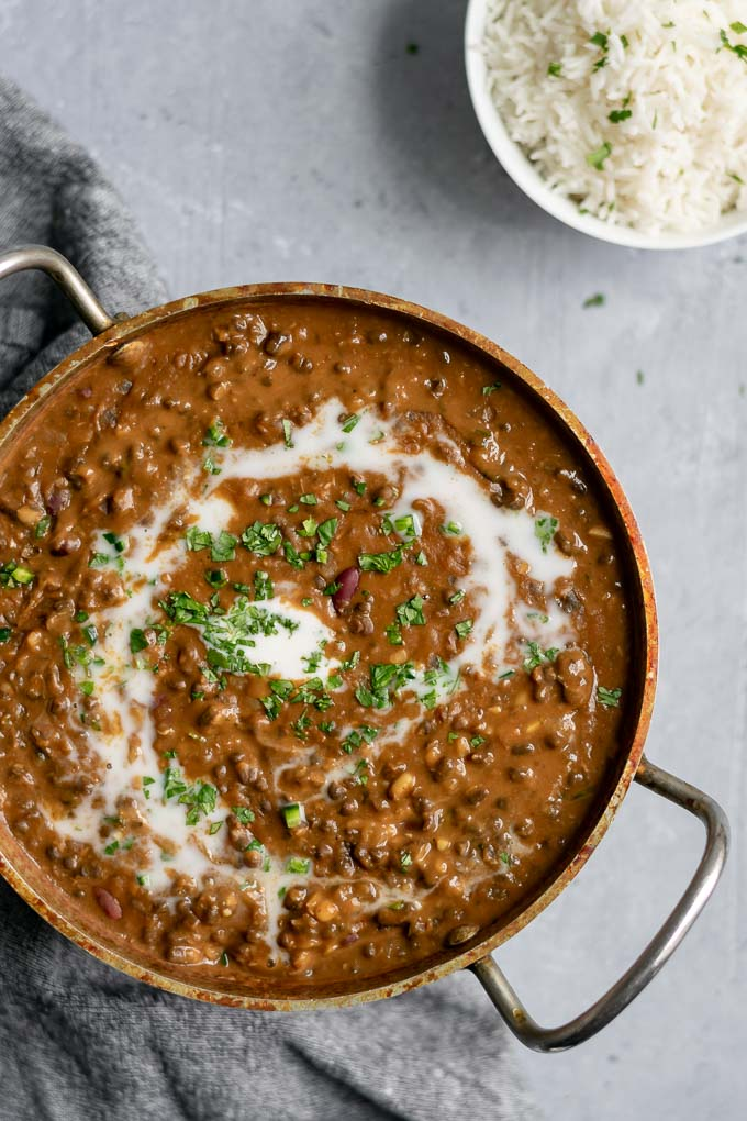 vegan dal makhani with a swirl of coconut milk and garnished with cilantro served with a bowl of basmati rice