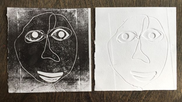 two embossed faces, one with ink rolled over