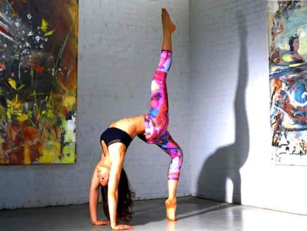 Woman doing yoga one legged wheel pose.