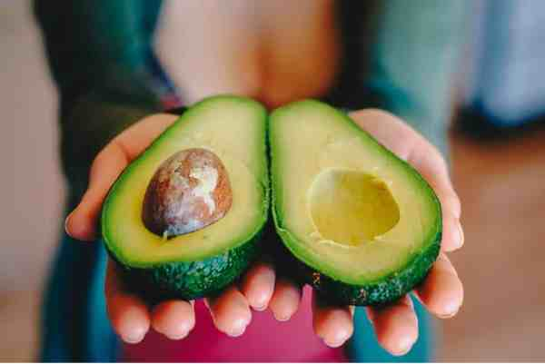 woman holding avocado cut in two