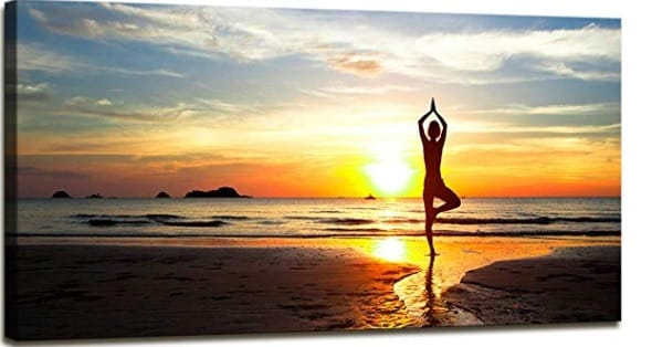 yoga canvas wall art with a woman doing yoga by the ocean