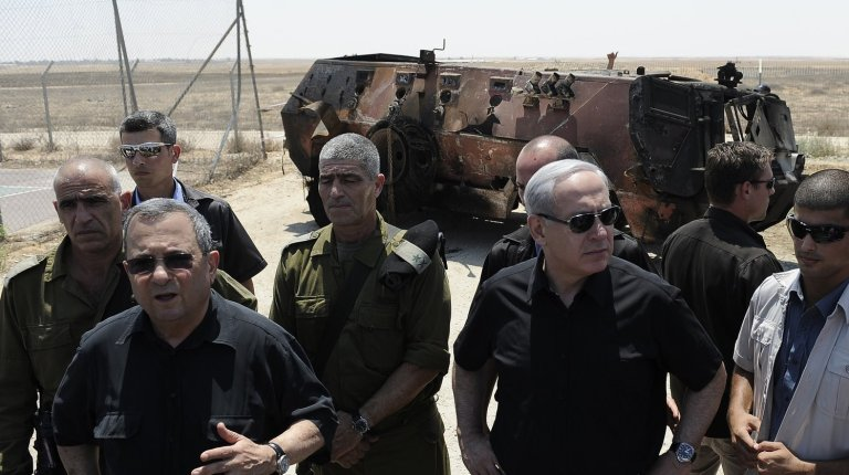 Israeli Defence Minister Ehud Barak (2nd L) and Prime Minister Benjamin Netanyahu (3rd R) speak to the press next to a burnt armoured vehicle near the Kerem Shalom border crossing after unidentified gunmen crossed into Israel from Egypt on 6 August AFP PHOTO / DAVID BUIMOVITCH