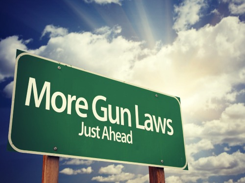 More Gun Laws Green Road Sign With Dramatic Clouds and Sky.