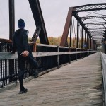 a person stretching in preparation for a run across a long bridge