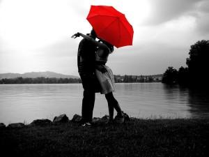 couple kissing under red umbrella