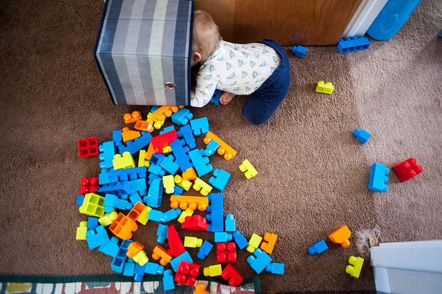 A small human ignores the mess of blocks to play in an empty box instead.