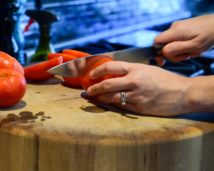 Slicing tomatoes in half.
