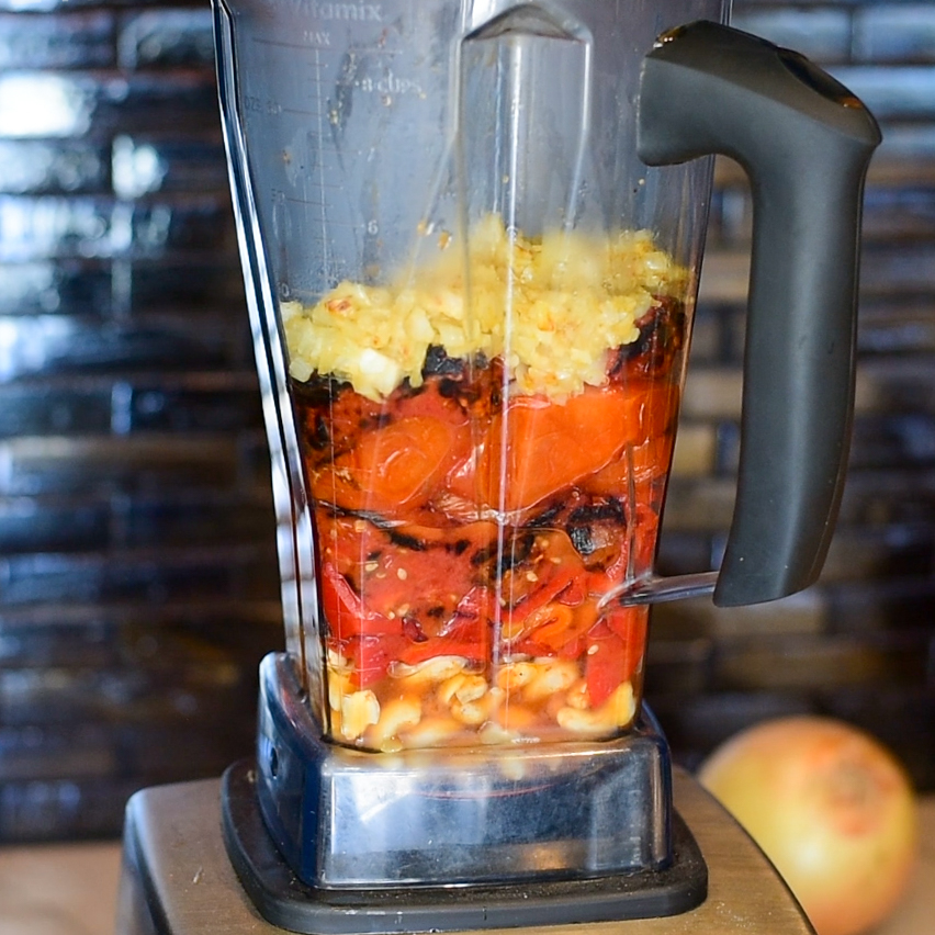 Layered ingredients in the blender for Roasted Tomato & Red Pepper Soup, including soaked cashews, roasted tomato & red pepper, sauteed onions and garlic.
