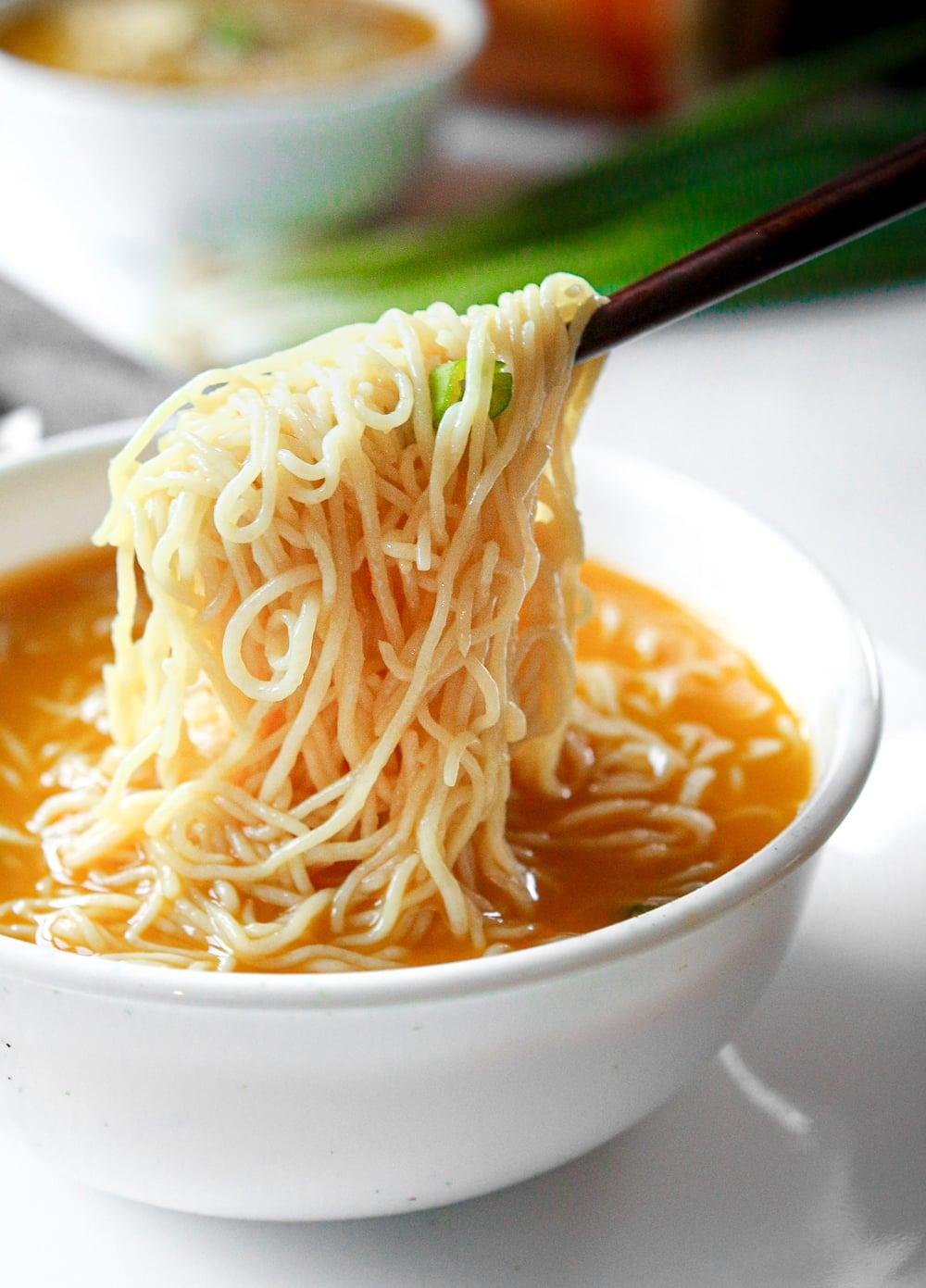 Chopsticks holding noodles above soup.