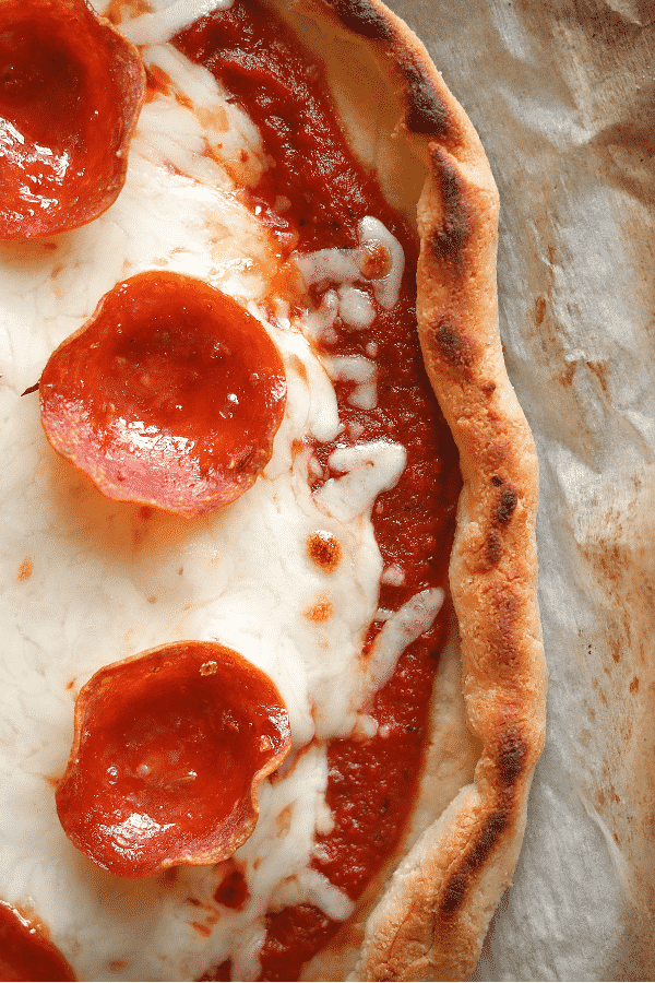 A side view of a cheese and pepperoni pizza on parchment paper. The pizza isn't cut into slices.