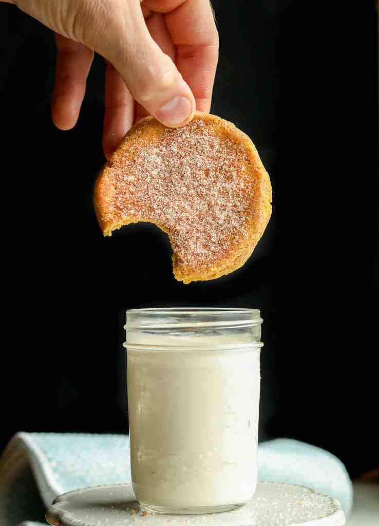 A pumpkin spice cookie with a bite taken out of it about to be dipped in a glass of milk.