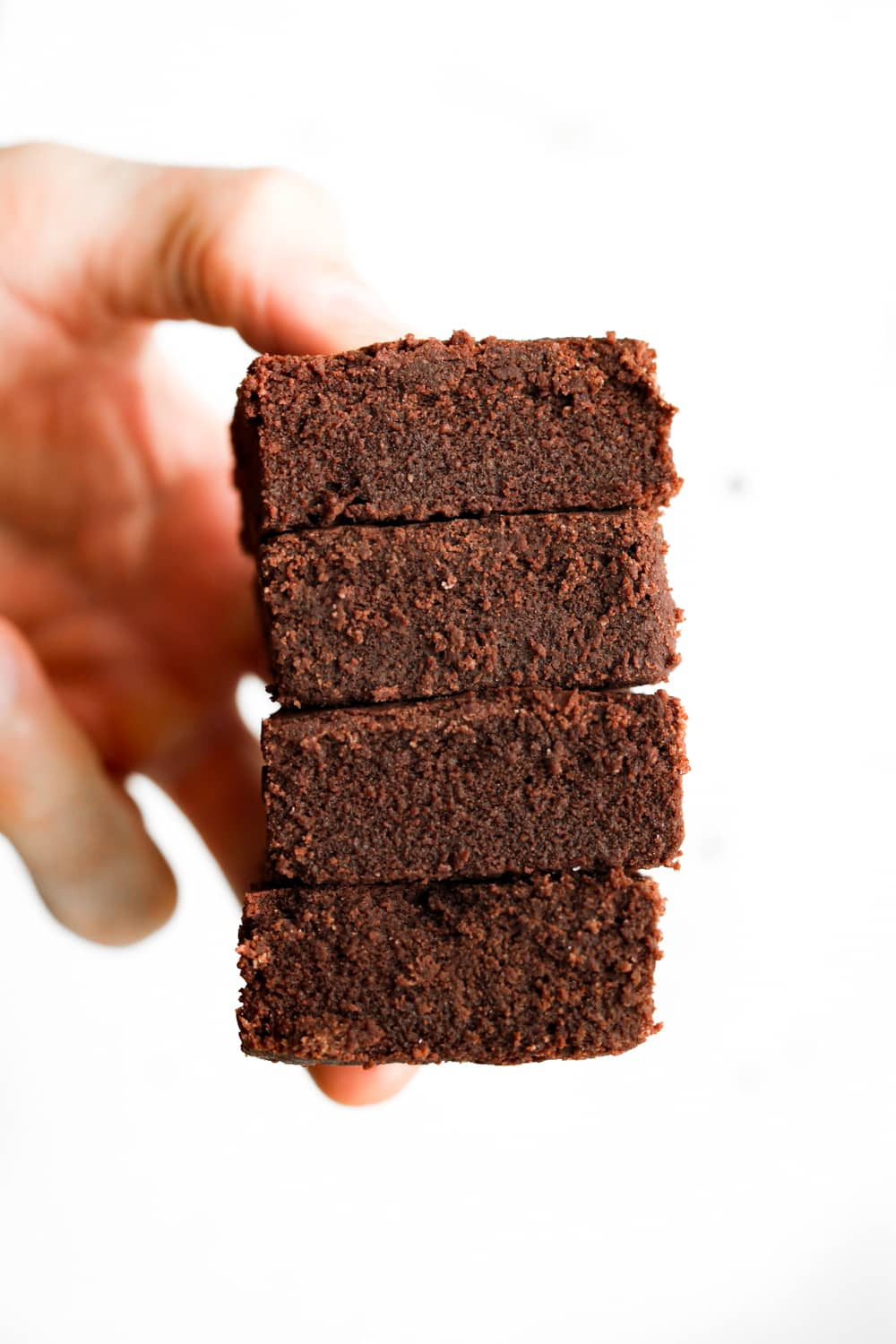 A hand holding fudgy coconut flour keto brownies