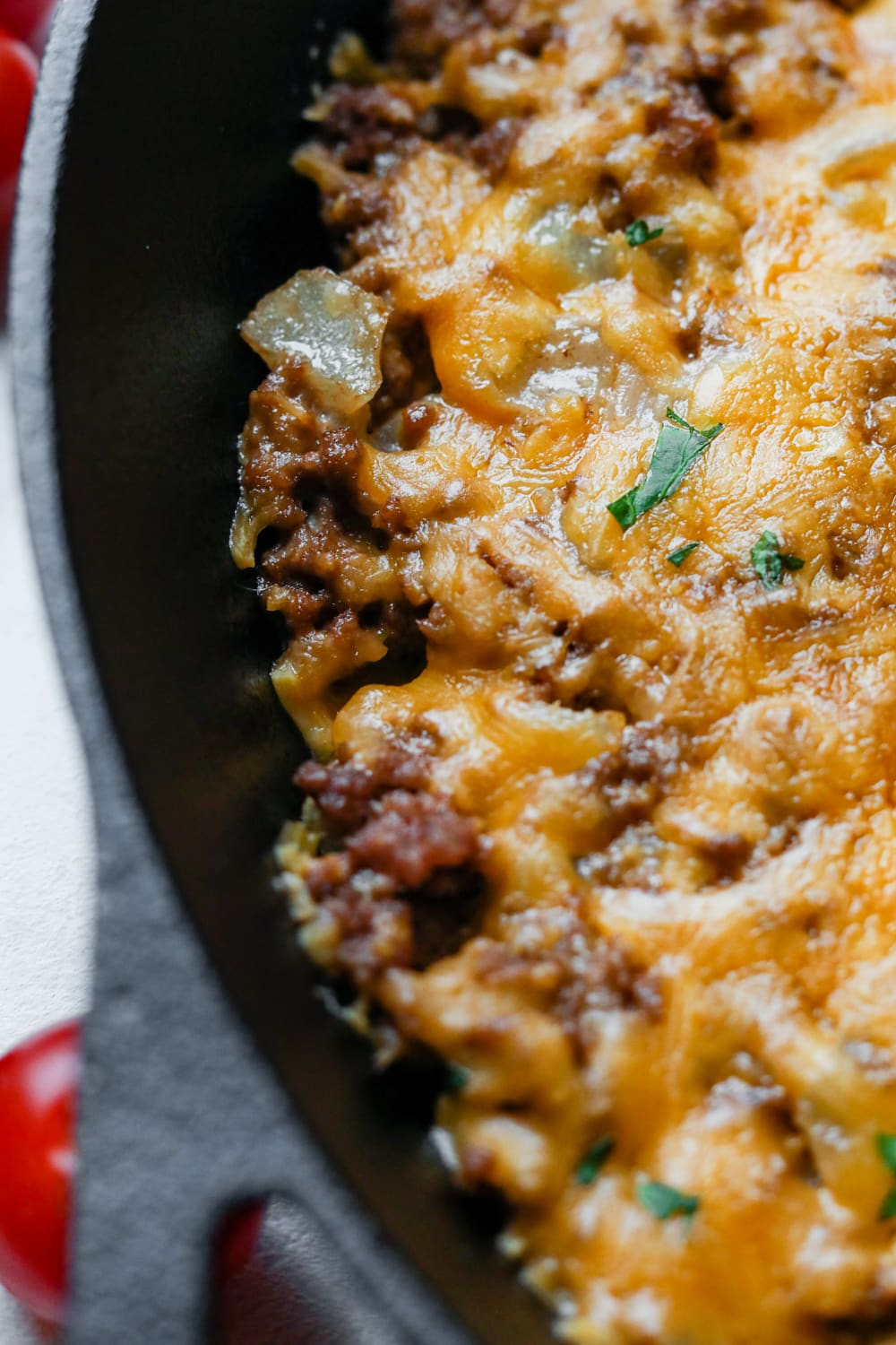 The edge of a pan with filled with ground beef, onions, and topped with cheddar cheese and chives.