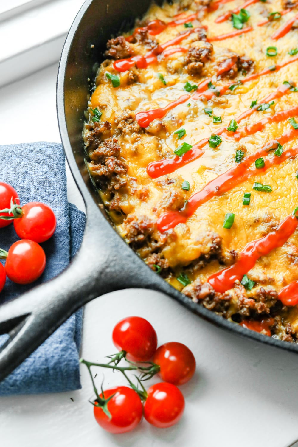 A cheeseburger casserole topped with chives and low carb ketchup