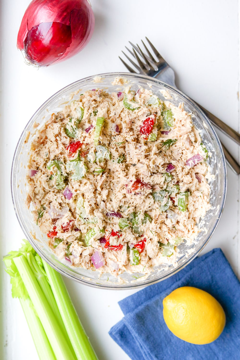 A large bowl of keto tuna salad with vegetables, a lemon, and two forks next to it.