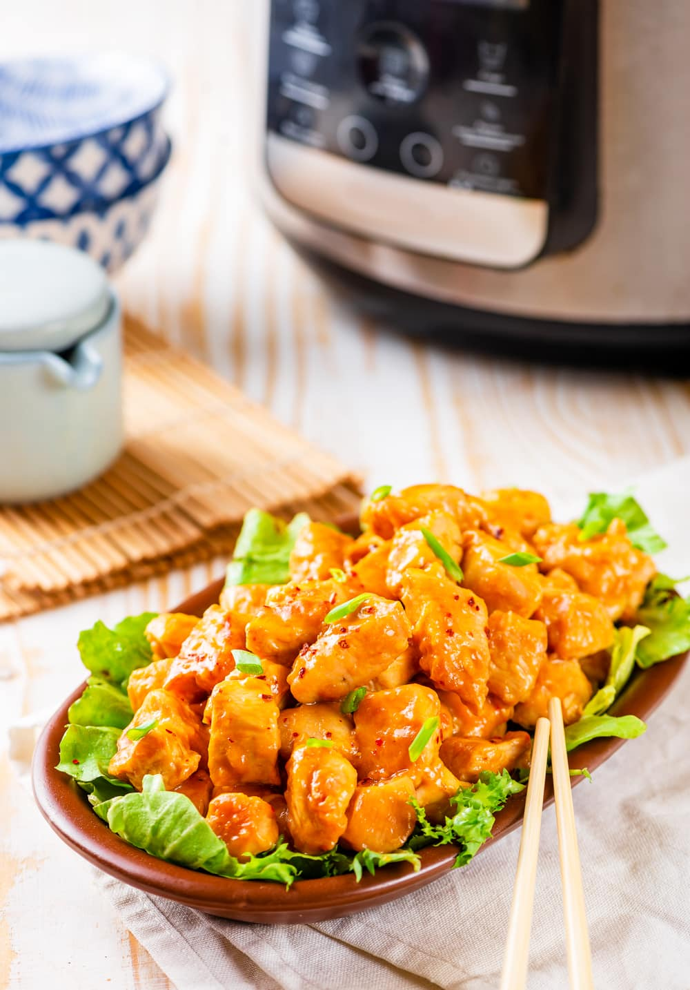 A bowl of orange chicken with an Instant Pot behind it.