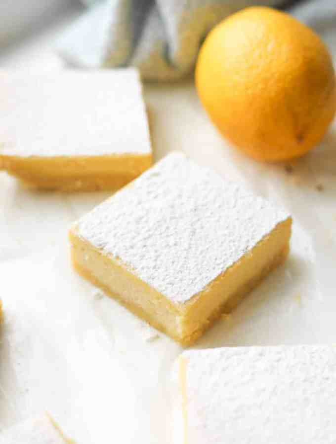 Lemon bars on parchment paper next to a lemon.