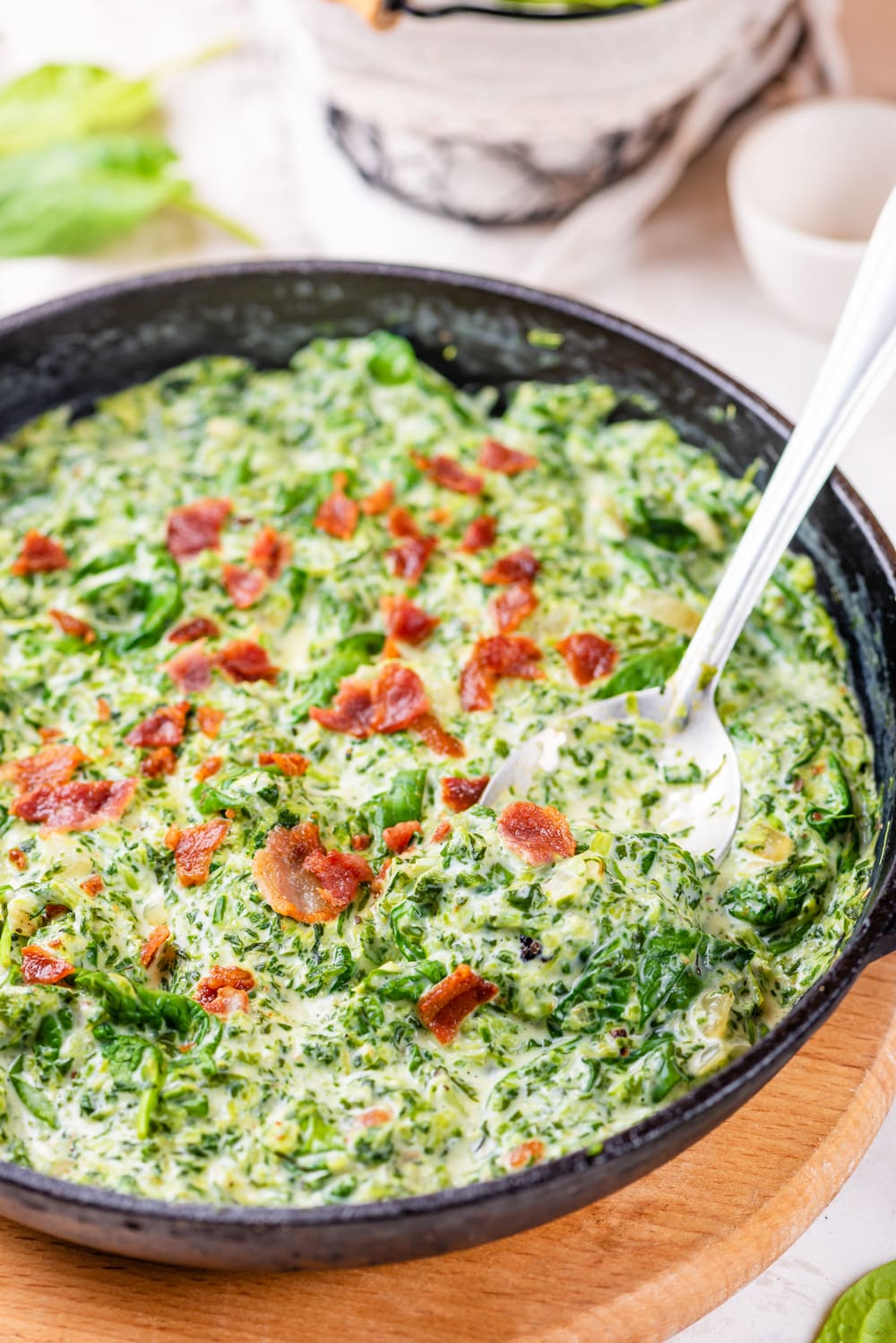 A cast iron pan filled with creamed spinach and bacon crumbles with a spoon for serving in the pan.