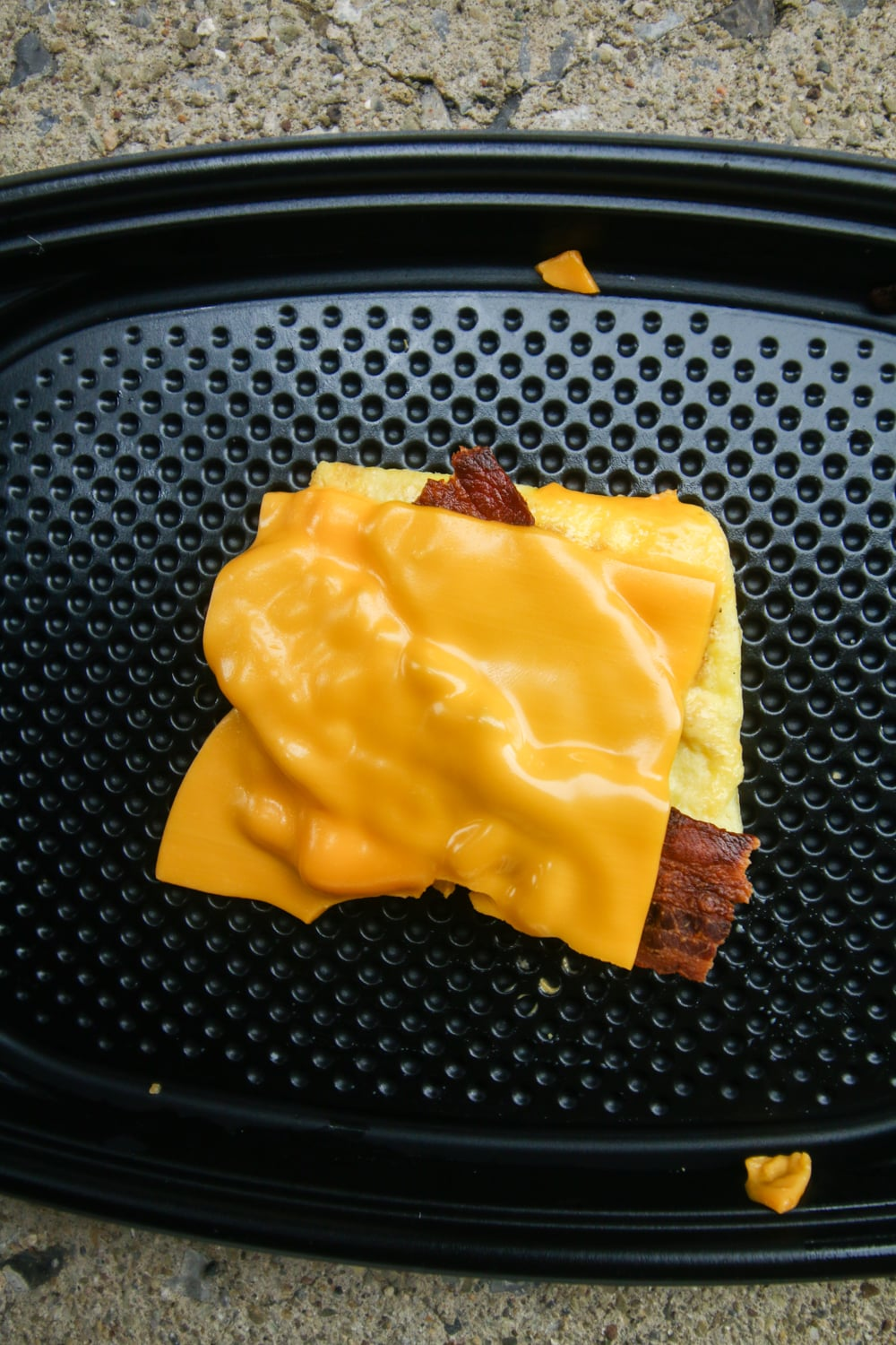 2 Slices of bacon on top of a folded egg and topped with American cheese.