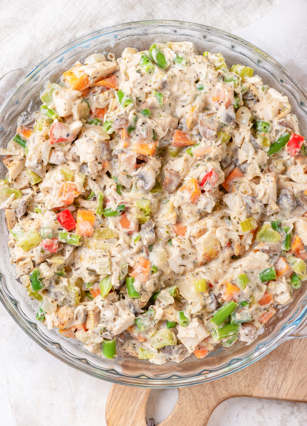 A bowl full of cooked vegetables, chicken, and cream cheese all mixed together.