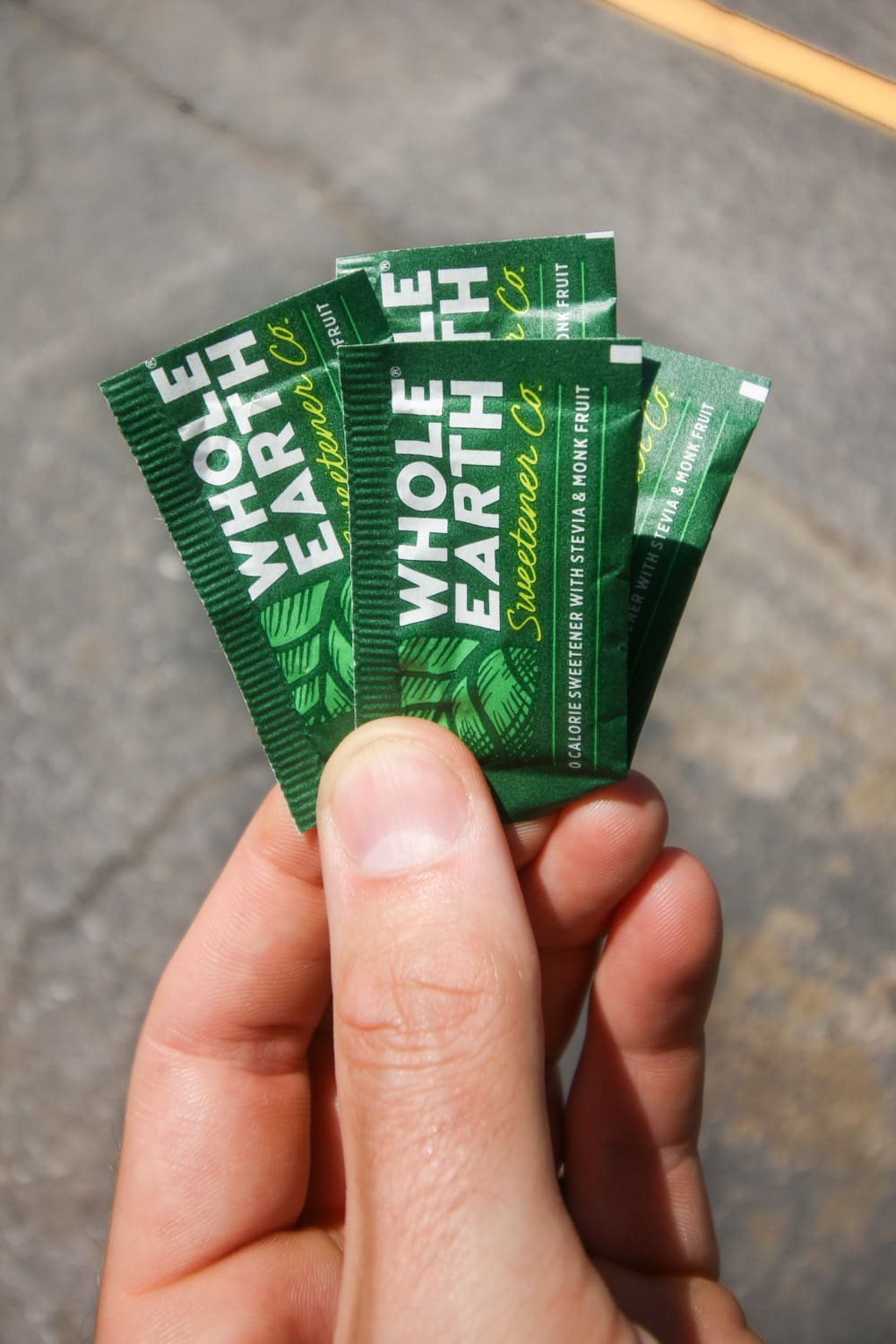 0 Carb sweetener packets being held by a hand.
