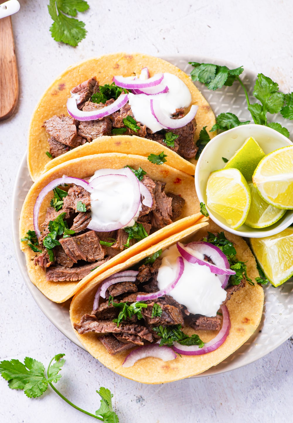 3 carne asada tacos on a plate next to a small bowl of cut up limes.