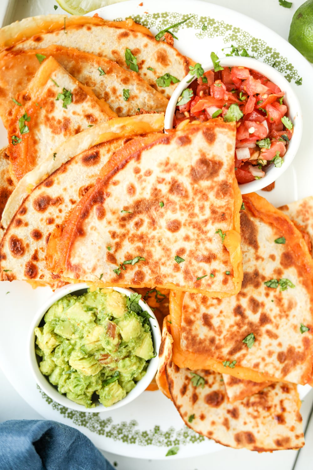 Cheese quesadillas on a white plate stacked on top of one another.