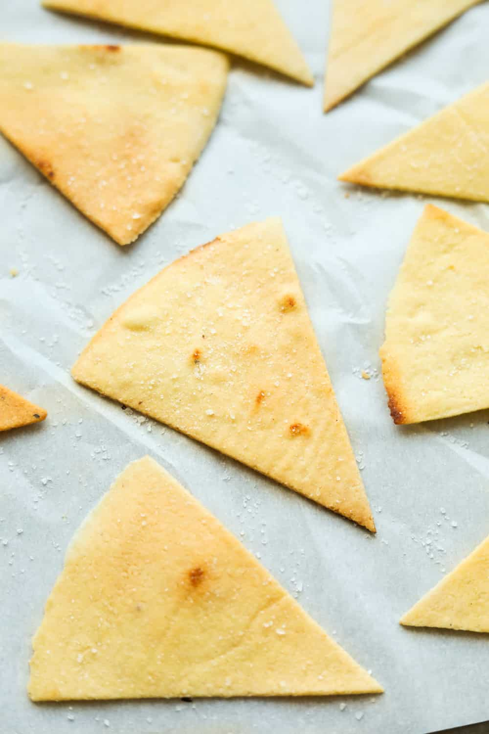 Tortilla chips on white parchment paper.