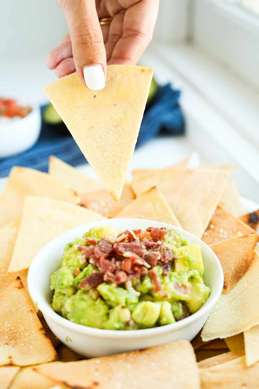 A hand holding a tortilla chip above a small of guacamole that's been topped with bacon.