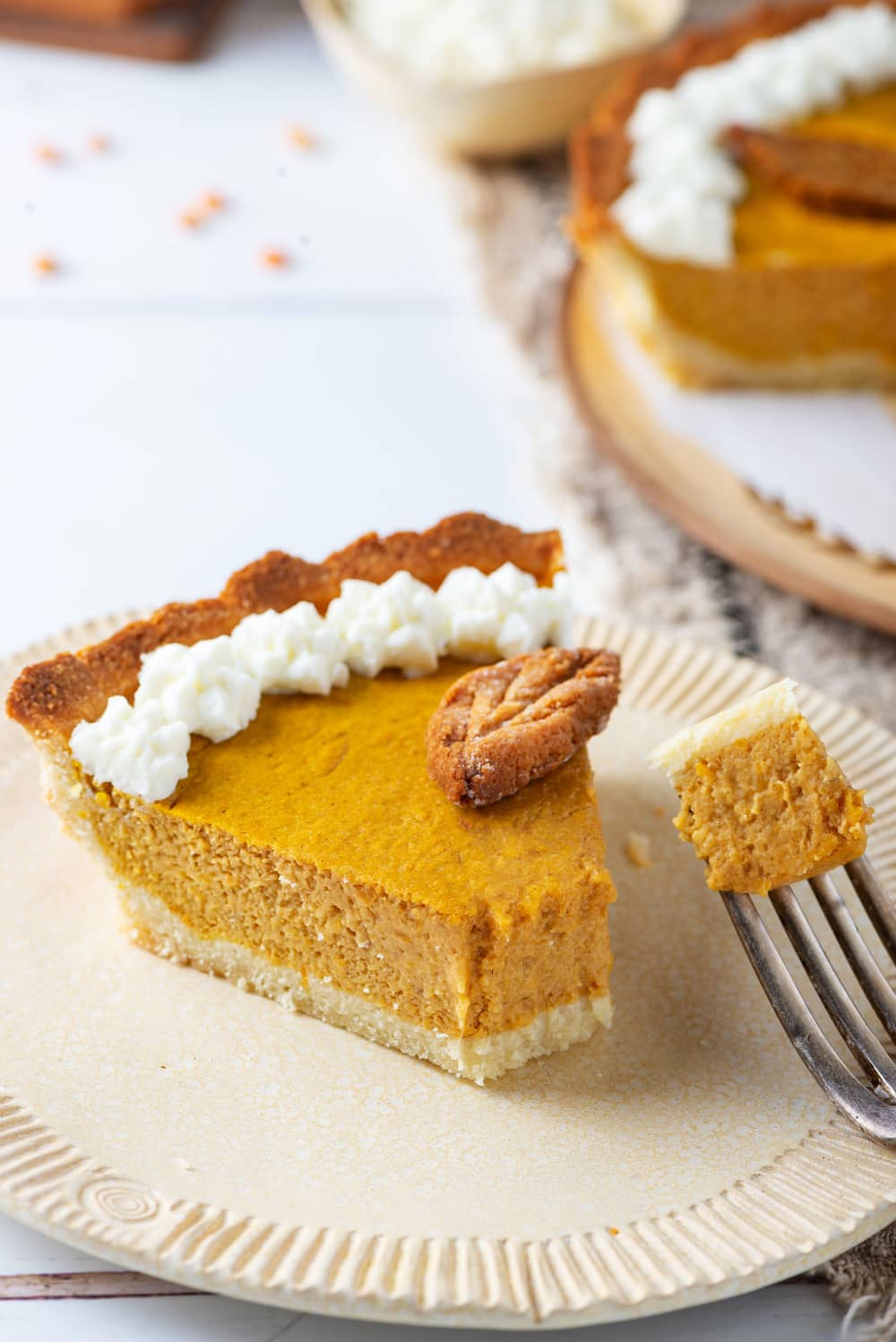 A plate with a slice of pumpkin pie, and a fork holding a piece of the pie next to it.