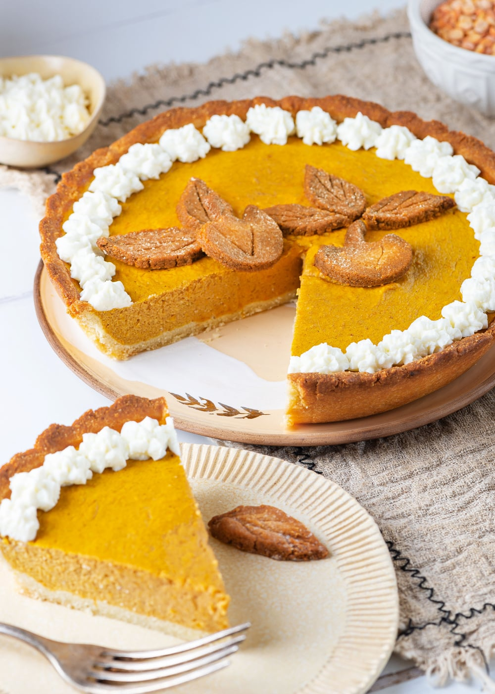 A slice of pumpkin pie set next to the rest of the pie.
