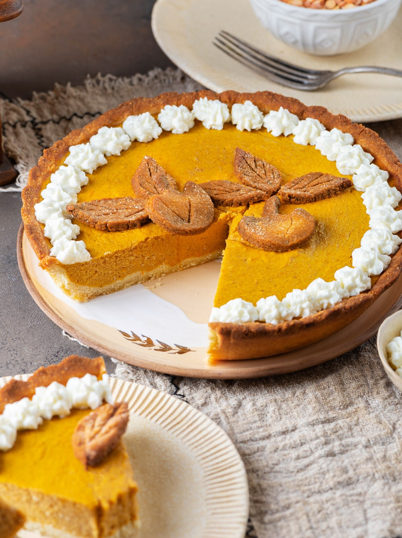A pumpkin pie that's missing a piece set on a serving plate.